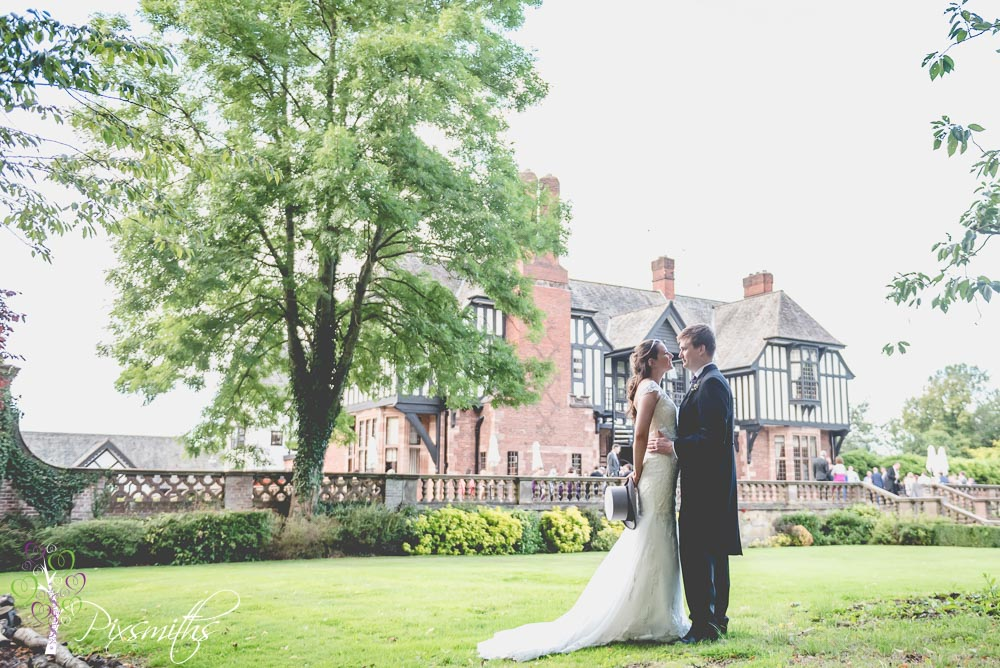lovely bride and groom shot with Inglewood MAnor wedding venue behind them