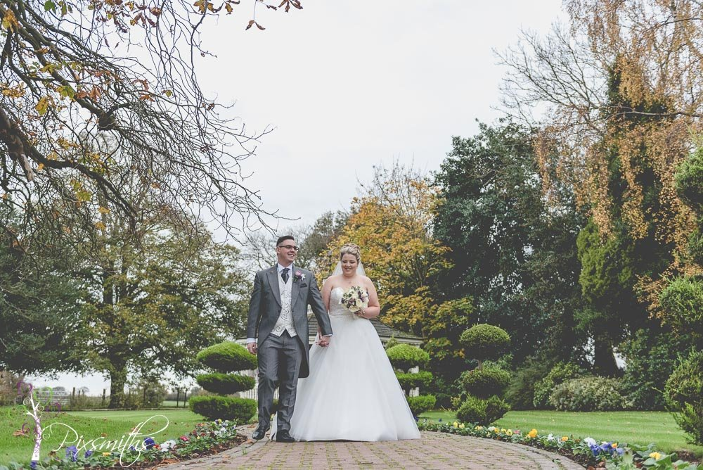 bride and groom strolling in gardens of Thornton Hall Hotel