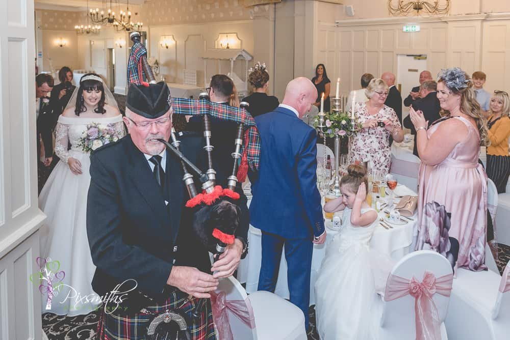 Leassowe Castle wedding reception, couple ushered in by bagpiper