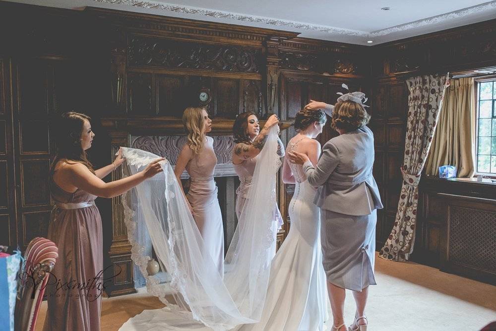 veil going on bride aided by maids and mum Inglewood Manor wedding